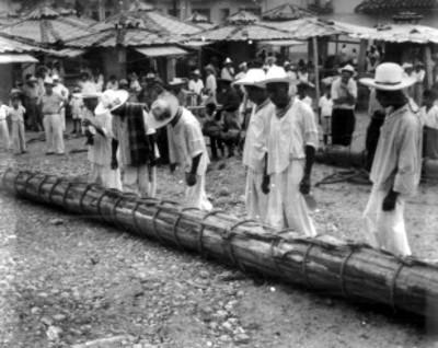Indios totonacas junto a tronco amarrado con cuerda