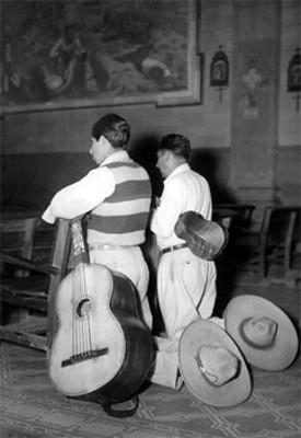 Músicos rezan hincados en una iglesia