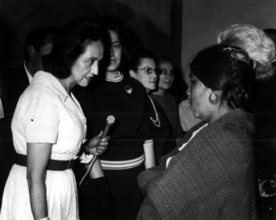 Eva Sámano de López Mateos conversa con mujer campesina durante evento de asistencia social