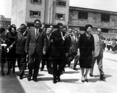 Adolfo López Mateos saluda a su paso durante su visita a un centro escolar