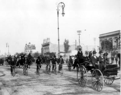 Hombres circulan a bordo de carruajes y bicicletas por el Paseo de la Reforma