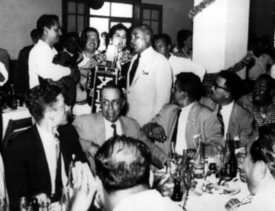 Emilio Portes Gil acompaña a un cantante durante, un banquete