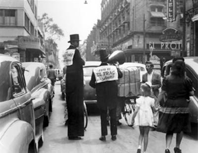 Hombres promocionan ropa para caballeros y un cine en una calle
