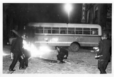 Soldados junto a camión incendiado por estudiantes, vista nocturna