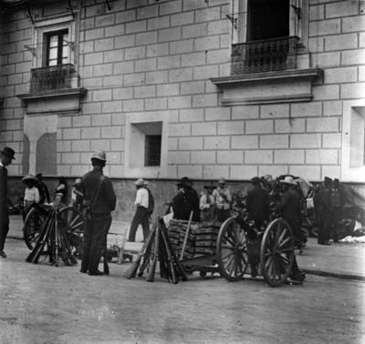 Soldados y civiles observan cañones y rifles en una calle
