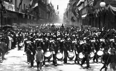 Banda de Guerra y militares desfilan por una calle