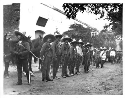 Revolucionarios zapatistas con caballos afuera de una hacienda