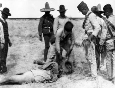 Soldados federales levantan cadáveres del campo de batalla