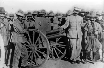 Francisco Villa y revolucionarios de pie junto a la artillería, retrato de grupo