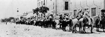 Revolucionarios a caballo, formados en una calle