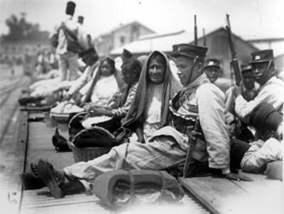 Soldados y mujeres viajan en los techos de un ferrocarril