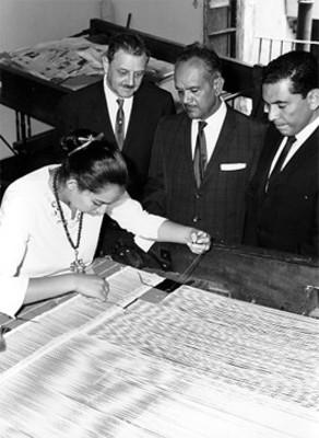 José Garibay y hombres observan a artesana con telar