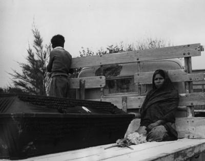 Mujer y niño junto a ataud sobre camión de redilas