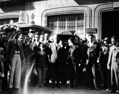 Hombres cargan féretro en una calle