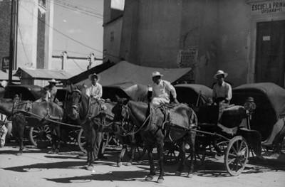 """Cocheros abordo de carruajes estacionados en una calle de """"San Juan del Río"""""""