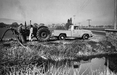 Agricultores riegan con un tractor