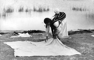 Mujer tiende su ropa a la orilla de un río