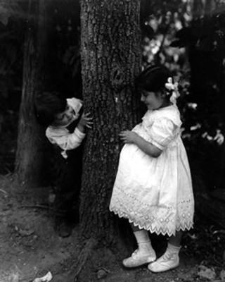 Niños juegan junto a un árbol