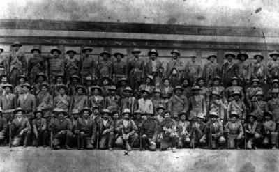 Francisco Villa y su Estado Mayor frente vagón de ferrocarril, retrato de grupo