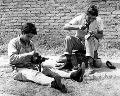 Hombres reparan calzado en una calle
