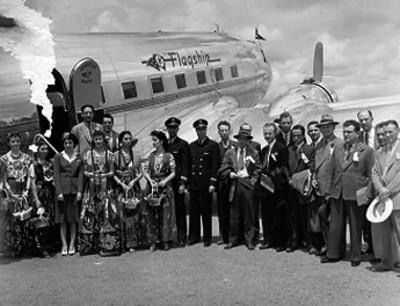 Diplomaticos, chinas poblanas y sobrecargos junto a un avión, retrato de grupo