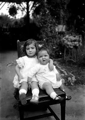 Hijos de Manuel Pérez Treviño sentados en una silla en un jardín, retrato