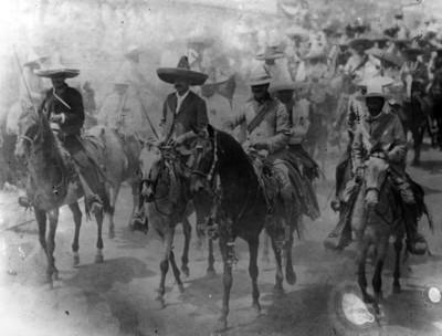 Eufemio Zapata y Alfonso Miranda avanzan por una calle a caballo