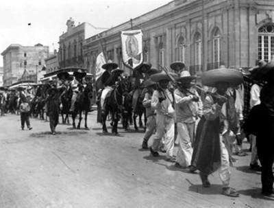 Fuerzas surianas con estandarte de la Virgen de Guadalupe desfilan por las calles de la ciudad