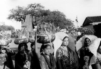 Tehuanas con arreglos florales caminan por un poblado