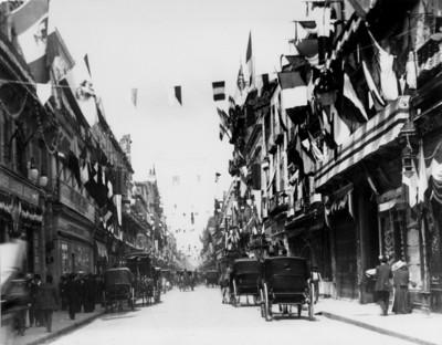 Carruajes y carros transitan por una calle