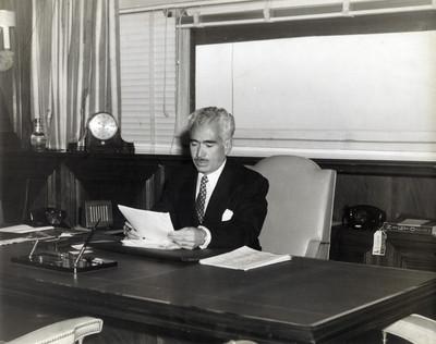 Ing. Raul Chávez lee documento sentado frente a escritorio