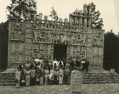 Grupo de personas frente a la reproducción de la Estructura ll de Hochob