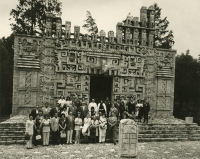 Grupo de personas frente a la reproducción de la estructura II de Hochob en el Museo de Antropología