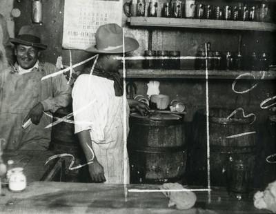 Hombre llena una tarro con pulque de un barril