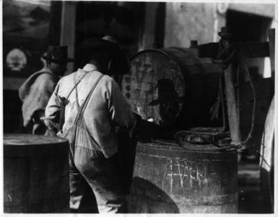 Hombres estiban barriles de pulque