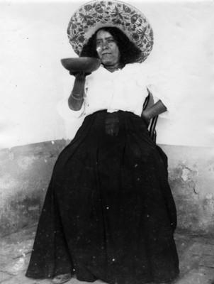 Mujer bebe pulque en jícara