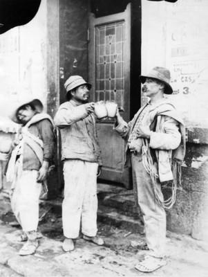 Hombres brindan con pulque fuera de una pulquería