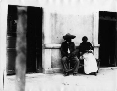 Hombre y mujer sentados en una banca afuera de pulquería