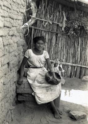 Tehuana con jícara sentada junto a vivienda indígena