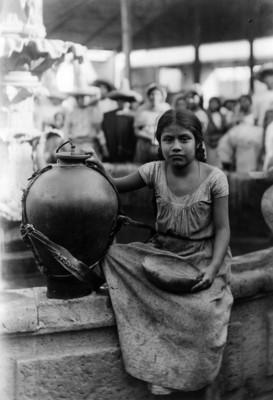 Niña Indígena con cantaro y jicara sentada en la orilla de una fuente