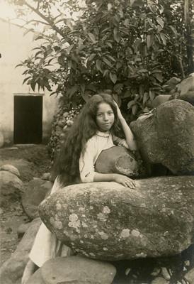Muchacha con cabello largo recargada en unas rocas