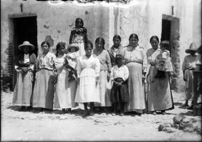 Mujeres y niños afuera de una casa, retrato de grupo