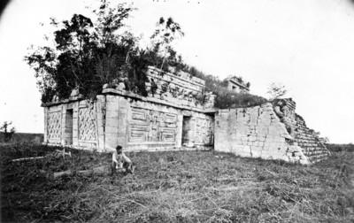 Hombre sentado junto a un edificio maya de estilo Pucc