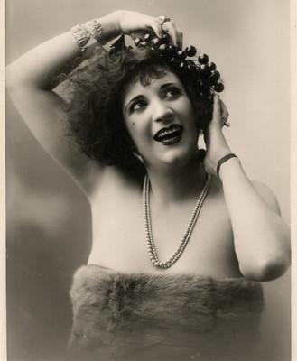 Celia Padilla con manos en tocado sobre su cabeza, retrato