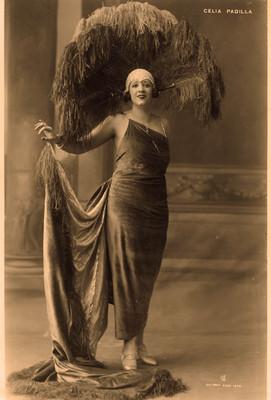 Celia Padilla con vestido largo y tocado de plumas, retrato