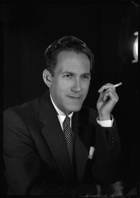 Gonzalo Curiel con rostro de perfil tres cuartos, sostiene un cigarrillo en su mano izquierda, retrato
