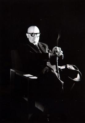 León Felipe sentado de perfil tres cuartos, con cigarrillo en la mano, retrato