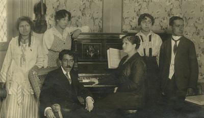 Profesores y alumnos de música junto a un piano, retrato de grupo