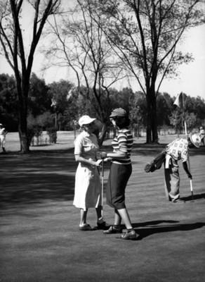 """Gene Wiestey con suéter"" platica con otra golfista"