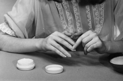 Mujer aplica crema en sus uñas